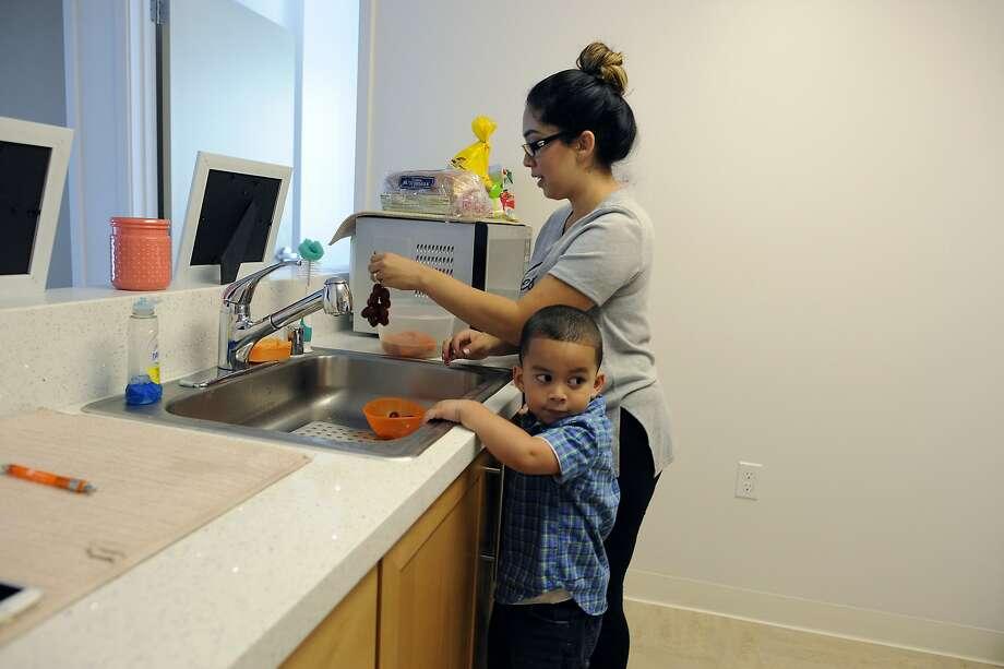 Jessia Pascasio rinses of a bunch of grapes for her son, Joshua Aleman, in the kitchen of their new two-bedroom apartment at the Beale Street Family Community, operated by Mercy Housing California, in San Francisco. Photo: Michael Short, Special To The Chronicle