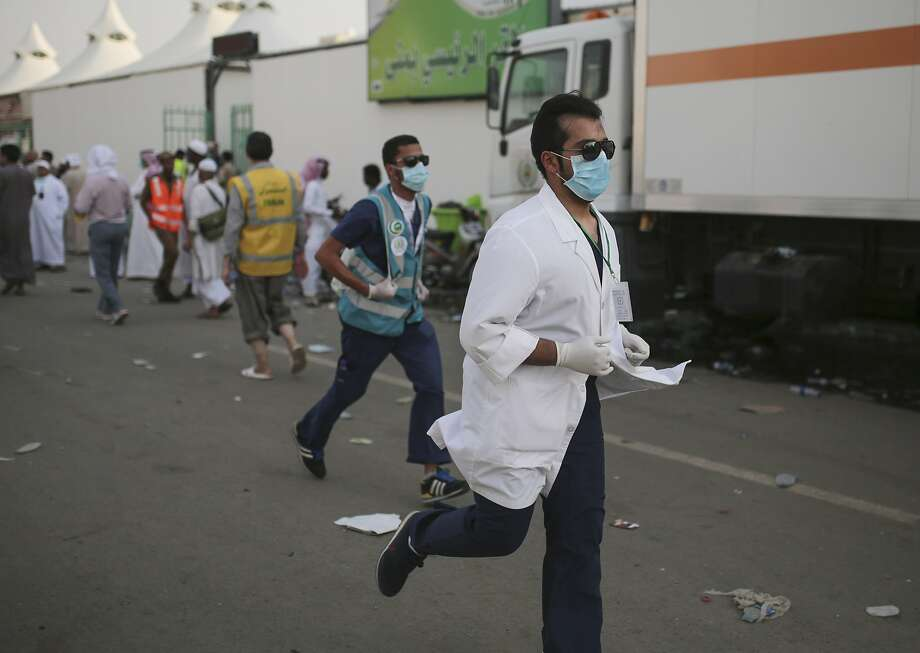 Medics rush to the site where pilgrims were crushed and trampled to death during the annual hajj pilgrimage in Mina, Saudi Arabia, Thursday, Sept. 24, 2015. The crush killed hundreds of pilgrims and injured hundreds more in Mina, a large valley on the outskirts of the holy city of Mecca, the deadliest tragedy to strike the pilgrimage in more than two decades. (AP Photo/Mosa'ab Elshamy) Photo: Mosa'ab Elshamy, Associated Press