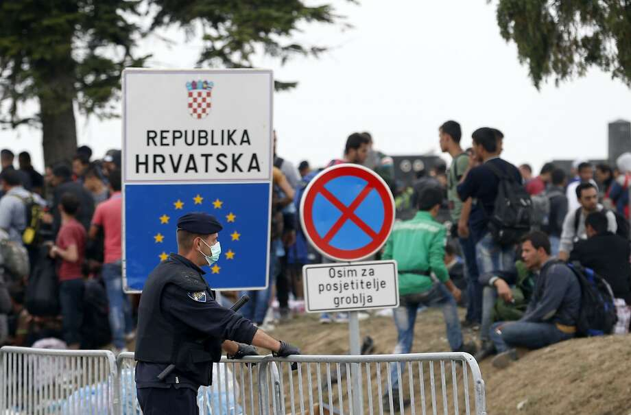 A Croatian policeman guards refugees at a Serbian cemetery on no-man's-land at a border crossing. Croatia has shut all but one of its crossings with Serbia to block the refugee surge. Photo: Darko Vojinovic, Associated Press
