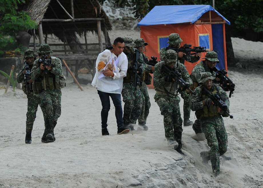 Philippine marines run as they simulate the rescue of a hostage as part of an amphibious raid and special-operations exercise by the navy at a marine training base in the town of Ternate in Cavite province. Photo: Ted Aljibe, AFP / Getty Images