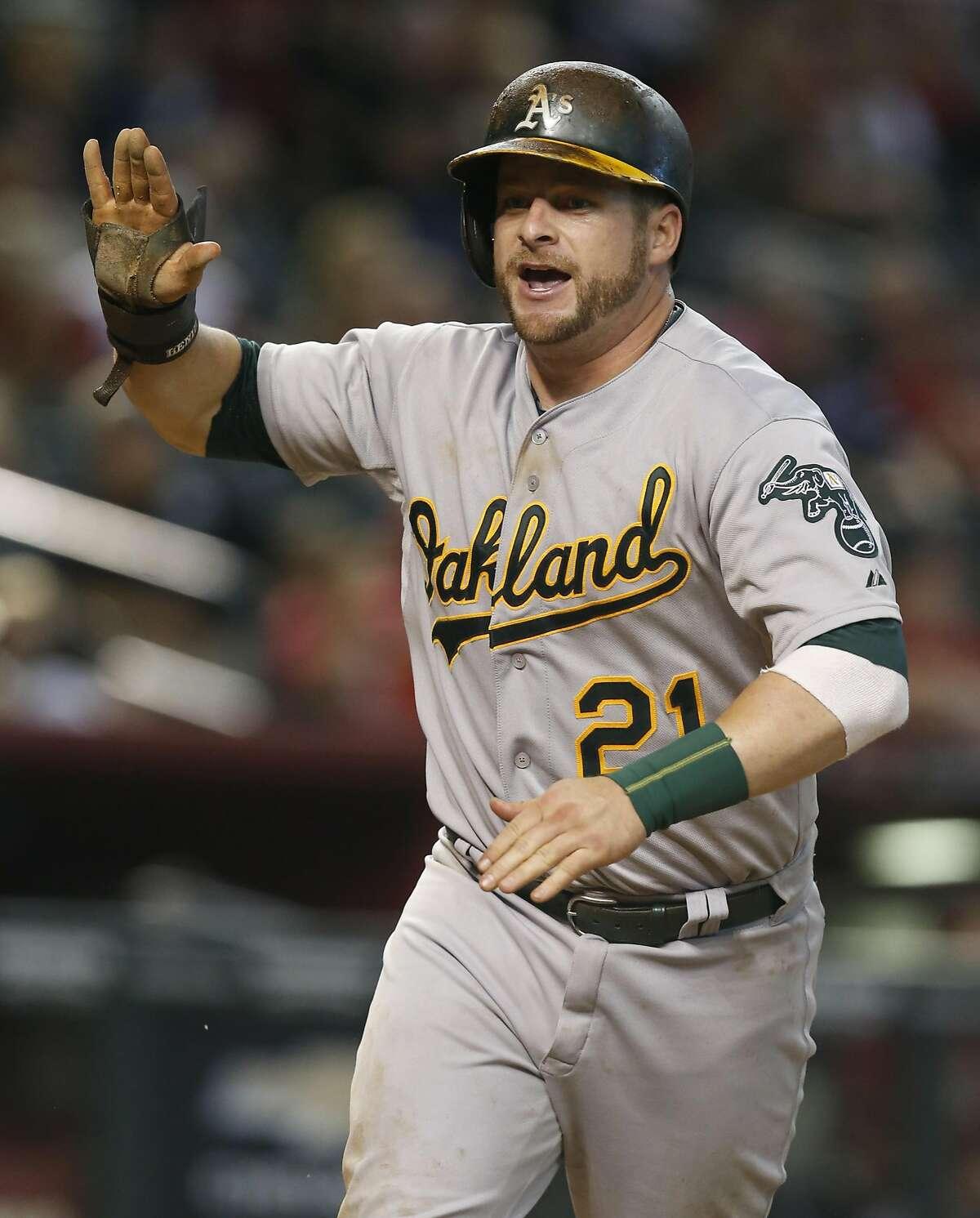 Oakland Athletics catcher Stephen Vogt (21) scores a run in the eleventh inning during a baseball game against the Arizona Diamondbacks, Sunday, Aug. 30, 2015, in Phoenix. (AP Photo/Rick Scuteri)