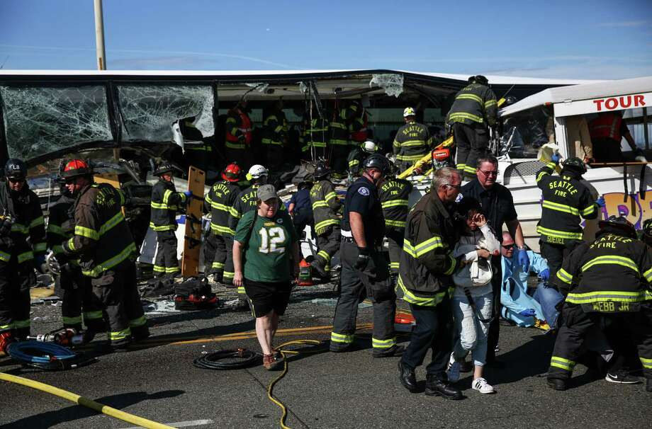First responders work the scene after a charter bus and a Ride the Ducks tour bus collided on the Aurora Bridge on Thursday, September 24, 2015. At least four were killed with scores injured in the horrific wreck. Photo: JOSHUA TRUJILLO, SEATTLEPI.COM / SEATTLEPI.COM