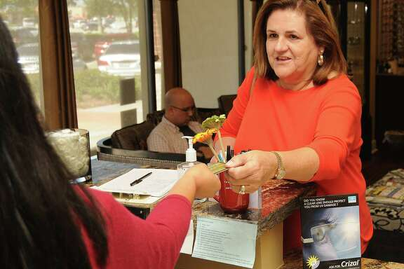 Kay Gutowsky uses her EMV card to pay for glasses at Eye Trends-€Barker Cypress on Saturday Sept. 19,2015.(Dave Rossman photo)