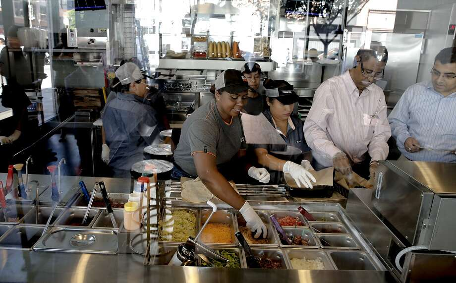 Cooks Janet Justo (center) and Arcadia Mariles prepare menu items at the newly opened Taco Bell Cantina, which is right by AT&T Park. Photo: Michael Macor, The Chronicle