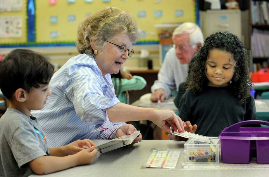 Laurie Schott works with Pedro Betances, 4, left, and Jeremih Cherry, 5, in a kindergarten class at Morris Street School in Danbury, Thursday, Sept. 24, 2015. Laurie and Charlie Schott of Brookfield, are volunteer mentors. Photo: Carol Kaliff / Hearst Connecticut Media / The News-Times