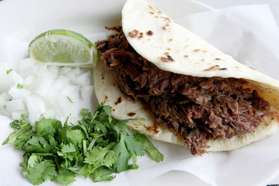 A barbacoa taco at El Milagrito includes minced cilantro, diced onions and a wedge of lime. Photo: Cynthia Esparza /For San Antonio Express-News / For San Antonio Express-News