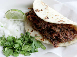 A barbacoa taco at El Milagrito includes minced cilantro, diced onions and a wedge of lime.