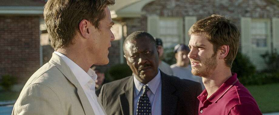 In the film, Michael Shannon (left) is real estate agent Rick Carver, who evicts and then hires Dennis Nash, played by Andrew Garfield (right). Photo: Associated Press
