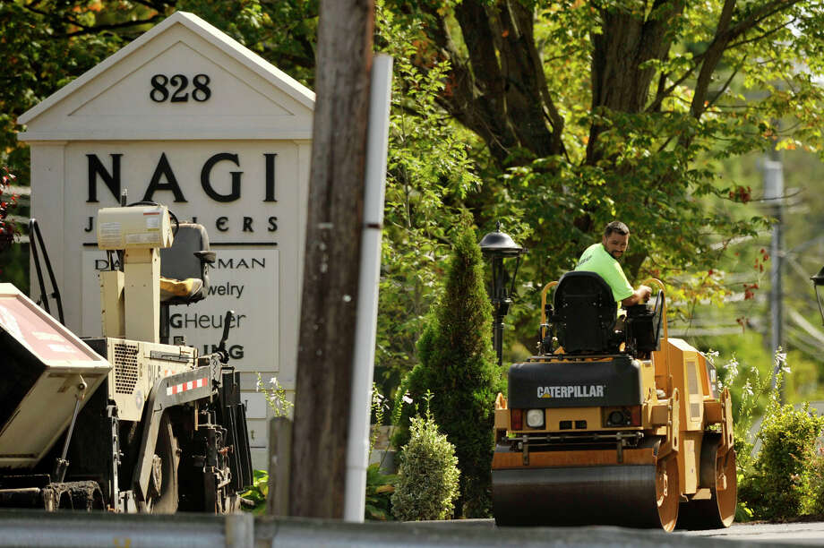 A construction crew resurfaces the parking area in front of Nagi Jewelers on High Ridge Road in Stamford on Monday. Photo: Jason Rearick / Hearst Connecticut Media / Stamford Advocate