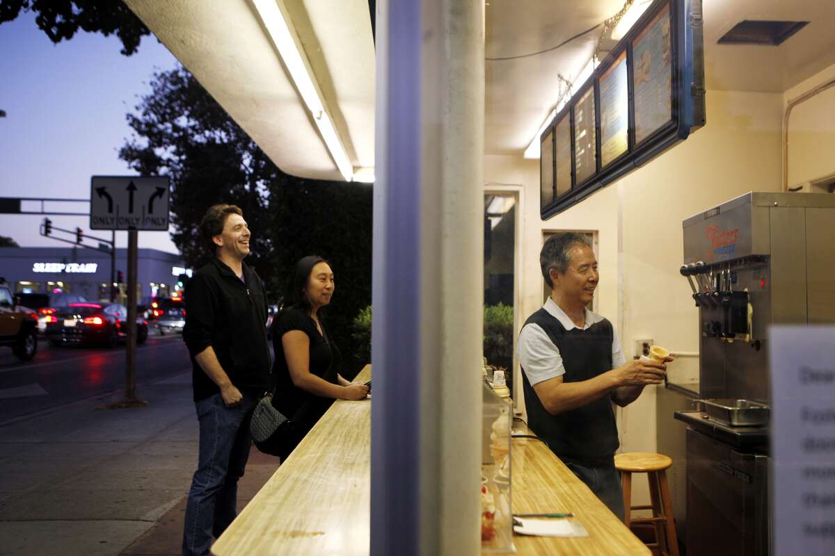 Mike Berman and Jessica Sison of Menlo Park, left, wait for owner Sung Lee, right, to prepare their ice cream on September 22, 2015.