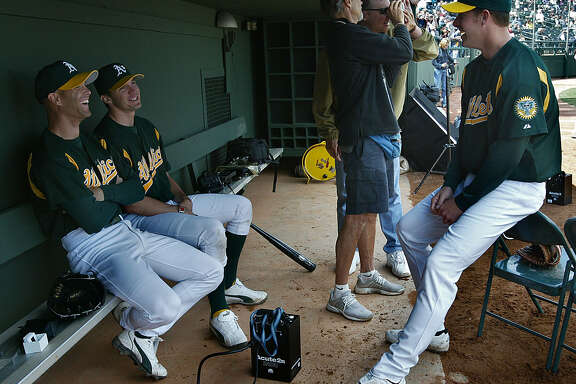 GIANTS3-C-02MAR03-SP-DF The Oakland Athletics star pitchers (l to r) Tim Hudson, Barry Zito, and Mark Mulder share a laugh after finishing a Sports Illustrated photo shoot with Walter Ioss (in black in background) who is showing a photo to Jim Young, with Media Relations for the Athletics before the Oakland Athletics play the San Francisco Giants at spring training in Phoenix, Arizona. CHRONICLE PHOTO BY DEANNE FITZMAURICE