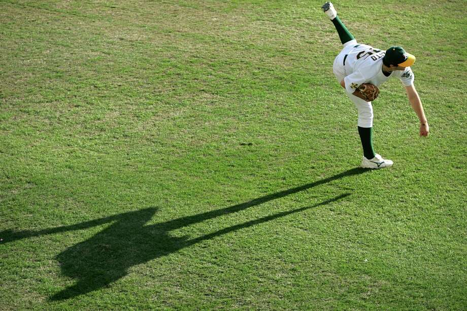 Then-A's starter Barry Zito warms up on the outfield grass on Oct. 10, 2006, in Oakland.  Photo: Kurt Rogers / SFC / The Chronicle