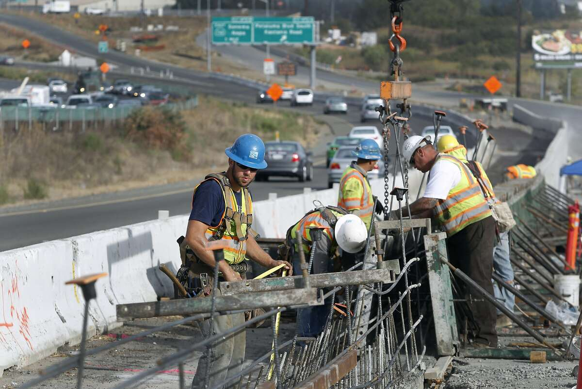 Construction workers build the shoulder barrier for the Highway 101 widening project near the Petaluma Boulevard South off-ramp in Petaluma, Calif. on Thursday, Sept. 24, 2015.