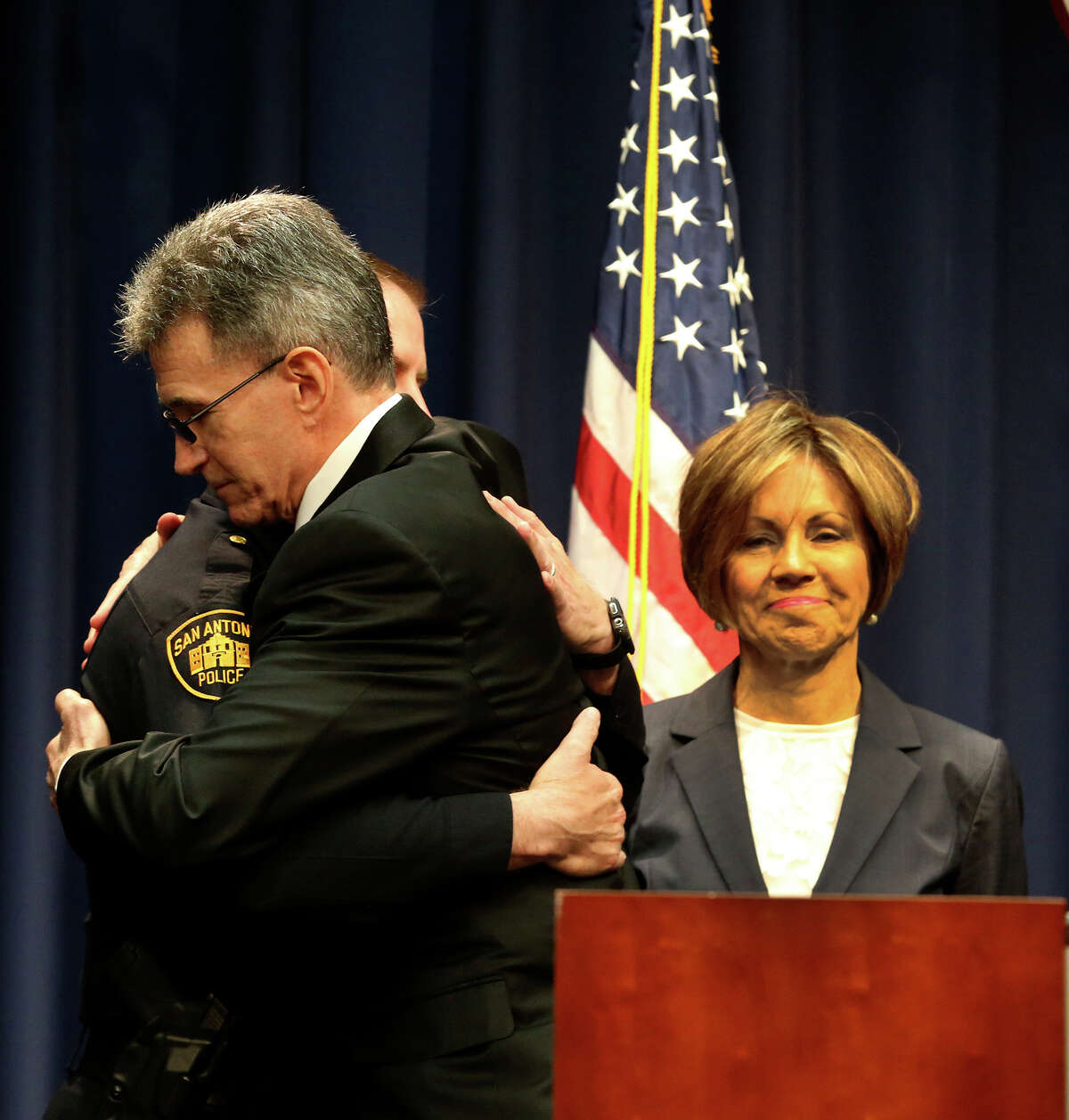 Former Police Chief Wiliam McManus (center) embraces interim Police Chief Anthony Trevino at City Hall after City Manager Sheryl Sculley announced her selection for the job.