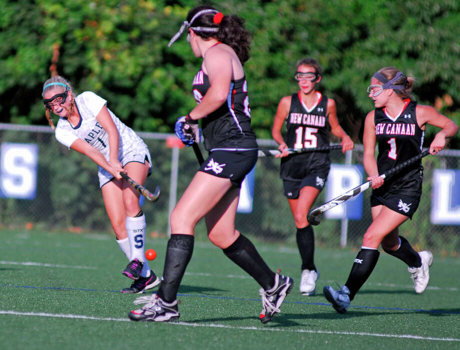 Staples' Jordan Ragland, left, hits the ball into a crowd of New Canaan players during a field hockey game on Thursday, Sept. 24th 2015 in Westport, Connecticut. The teams tied 3-3. Photo: Ryan Lacey/Staff Photo / Westport News Contributed