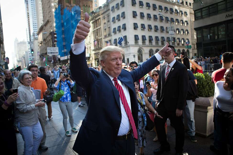 U.S. Presidential Candidate Donald Trump waves to the crowd gathered in front of the Trump Tower ahead of the arrival of the pope's motorcade Thursday, Sept. 24, 2015, in New York. (AP Photo/Kevin Hagen)