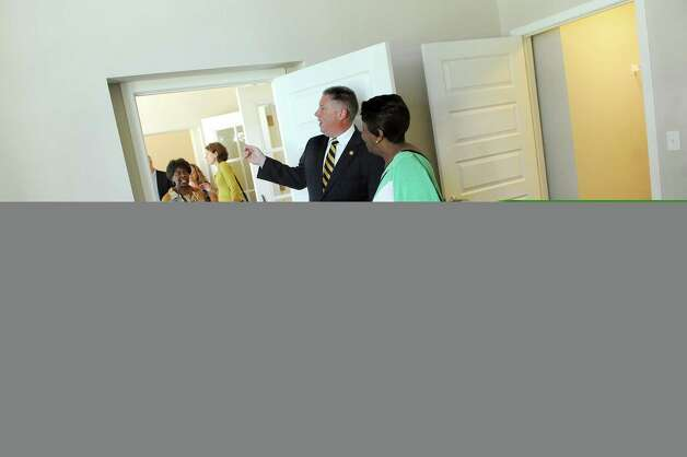 Assemblyman John T. McDonald III, center, joins Ernestine White, right, as they tour a one-bedroom apartment on Thursday, Sept. 24, 2015, at the Livingston School Apartments in Albany, N.Y. (Cindy Schultz / Times Union) Photo: Cindy Schultz / 00033472A