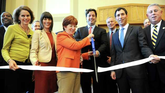 Joining other officials, Mayor Kathy Sheehan, center, and Gilbert Winn, CEO of Winn Companies, hold the scissors as they cut the ceremonial ribbon on Thursday, Sept. 24, 2015, at the Livingston School Apartments in Albany, N.Y. (Cindy Schultz / Times Union) Photo: Cindy Schultz / 00033472A