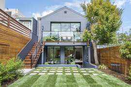 The south-facing backyard of 121 Clipper St. in Noe Valley includes a level lawn, a shade tree, raised deck and a patio.