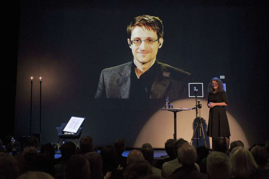 A giant screen displays the image of fugitive US intelligence contractor Edward Snowden as he is represented by an empty chair while being awarded the freedom of expression prize Bjornson in Molde, Norway, on September, 5, 2015. Hege Newth Nouri, president of the Norwegian Academy of Literature and Freedom of Expression to the right. AFP PHOTO / NTB SCANPIX / SVEIN OVE EKORNESVAAG +++ NORWAY OUTSVEIN OVE EKORNESVAAG/AFP/Getty Images ORG XMIT: 5876 Photo: SVEIN OVE EKORNESVAAG / Svein Ove Ekornesvaag