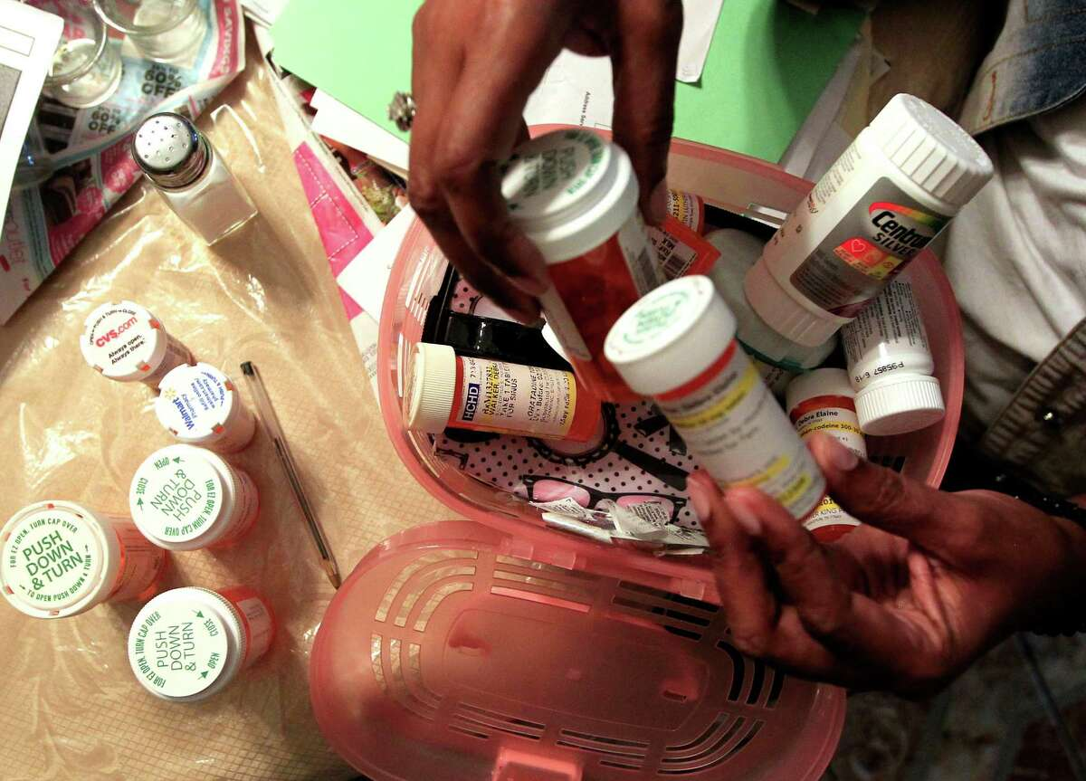 Debra Walker, a patient of the Harris Health system, goes over her medications in her Houston home on Thursday, Sept. 24, 2015. Debra Walker, a patient of Harris Health system, talks about how the changes in the eligibility rules will effect her in her home Thursday, Sept. 24, 2015, in Houston.