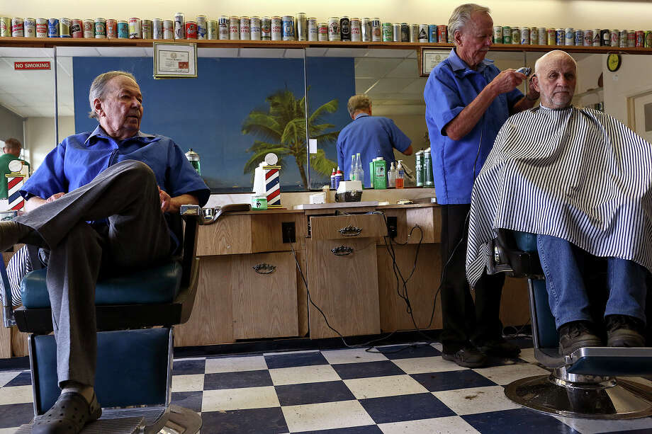 Harold Hedrick, left, watches as his twin brother, Harry, right, cuts the hair of John Warmowski, at their shop in San Antonio At 84, they are giving up the shop. Harold will retire; Harry will work part-time. Photo: Lisa Krantz, Staff / SAN ANTONIO EXPRESS-NEWS