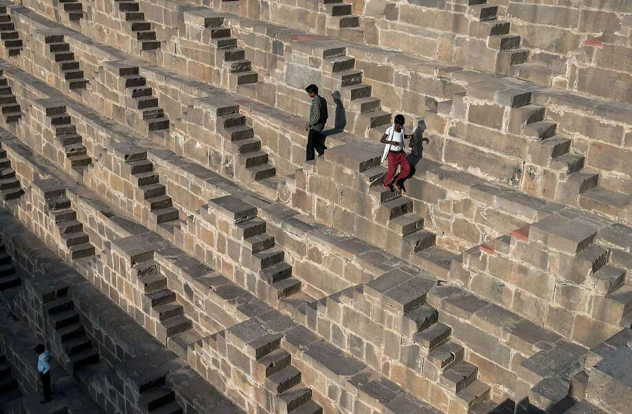 Indian men walk down the steps of the historic Chand Baori stepwell  in Abhaneri village of western Rajasthan state on September 24, 2015. For a few hours on one day each year, local residents are permitted to descend into the 100-foot-deep, 1,200-year-old stepwell, as Hindu devotees in the area mark a local festival, at the same time as Hindus worldwide observe Ganesh Chaturthi festivities. Chand Baori is one of the oldest and largest stepwells in the world, with some 3,500 steps laid out in a geometric design down to the water at its base. Photo: Alex Ogle, AFP / Getty Images