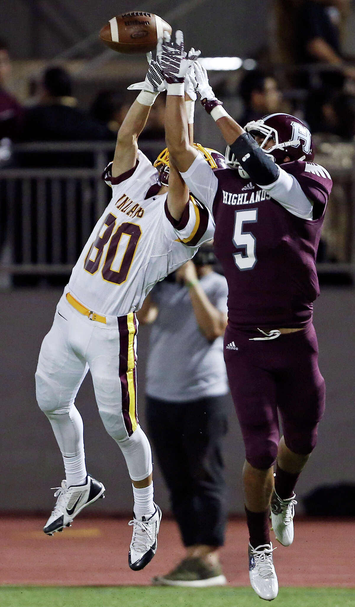 Harlandale's Rene Palomino goes up for a pass as he is defended by Highlands' Thomas Salame during second half action Friday Sept. 24, 2015 at Alamo Stadium. The pass was incomplete. Highlands won 14-7.