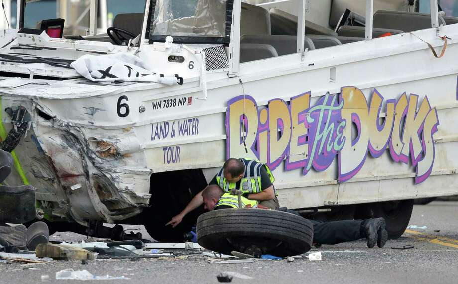 "Seattle Police officers look under a ""Ride the Ducks"" tourist vehicle as a tire and wheel from the bus sits nearby before the bus is loaded onto a flatbed tow truck Thursday, Sept. 24, 2015, after it was involved in a fatal crash with a charter passenger bus earlier in the day in Seattle. Photo: Ted S. Warren, AP / AP"