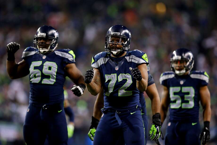 Defensive end Michael Bennett #72 of the Seattle Seahawks and defensive tackle Clinton McDonald #69 react against the San Francisco 49ers during the 2014 NFC Championship at CenturyLink Field on Jan. 19, 2014 in Seattle.  (Photo by Ronald Martinez/Getty Images)