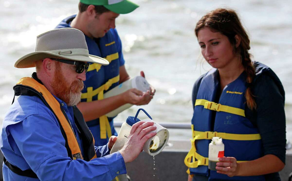 ADVANCE FOR USE SATURDAY, SEPT. 26, 2015 AND THEREAFTER - In this Tuesday, Sept. 15, 2015, photo, Thomas Bridgeman, an associate professor in the Department of Environmental Sciences at the University of Toledo, left, along with graduate students Kristen Hebebrand and Ken Gibbons, gather water samples from Lake Erie near the City of Toledo water intake crib, approximately 2.5 miles off the shore of Curtice, Ohio. In the wake of Toledo?'s water crisis, Ohio has put limits on when and where farmers can spread fertilizer and manure on fields. (AP Photo/Haraz N. Ghanbari) ORG XMIT: NY333