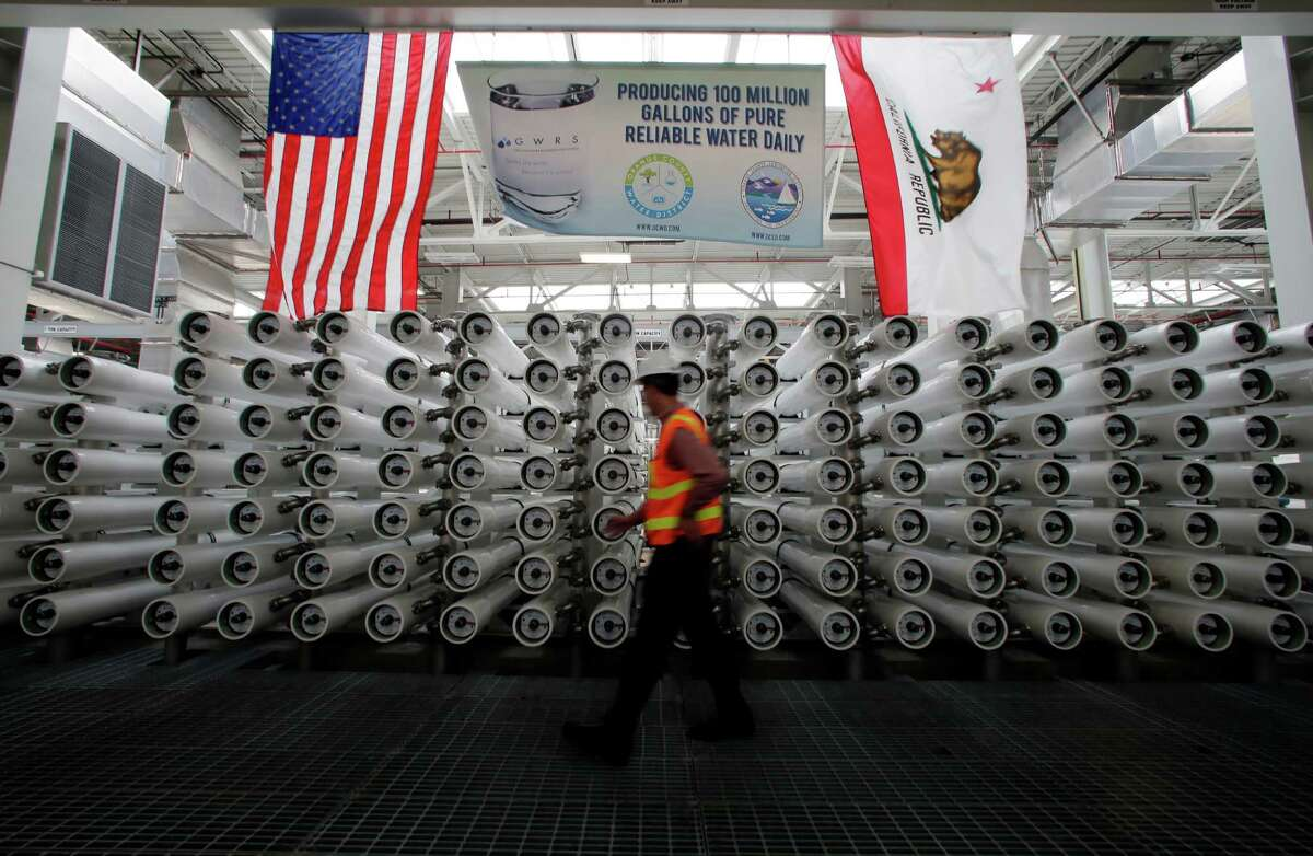 ADVANCE FOR USE SATURDAY, SEPT. 26, 2015 AND THEREAFTER - In this Wednesday, July 29, 2015, photo, Jason Dadakis of the Orange County Water District walks past part of the water filtration system at their water treatment plant in Fountain Valley, Calif. Orange County's myriad efforts to ensure its taps keep flowing can serve as a model for other communities across the nation where water is in short supply. (AP Photo/Chris Carlson) ORG XMIT: NY351