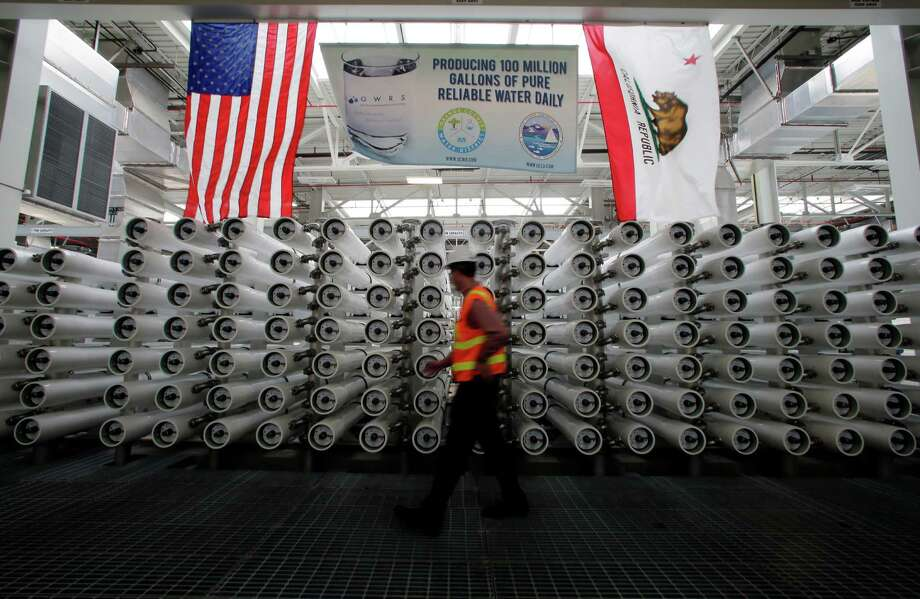 ADVANCE FOR USE SATURDAY, SEPT. 26, 2015 AND THEREAFTER - In this Wednesday, July 29, 2015, photo, Jason Dadakis of the Orange County Water District walks past part of the water filtration system at their water treatment plant in Fountain Valley, Calif. Orange County's myriad efforts to ensure its taps keep flowing can serve as a model for other communities across the nation where water is in short supply. (AP Photo/Chris Carlson) ORG XMIT: NY351 Photo: Chris Carlson / AP