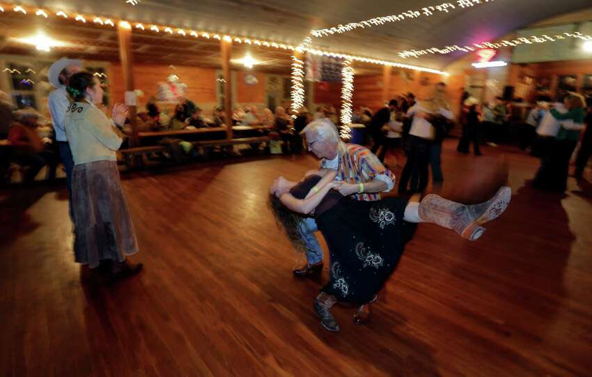 In this Dec. 6, 2014, photo, visitors dance to live music by Al Dressen's Super Swing Review at Twin Sisters Dance Hall in Blanco, Texas. A preservation group says old Texas dance halls that for years served as important social centers in rural areas of the state are decaying and closing, with comparatively few still operating. (AP Photo/Eric Gay)
