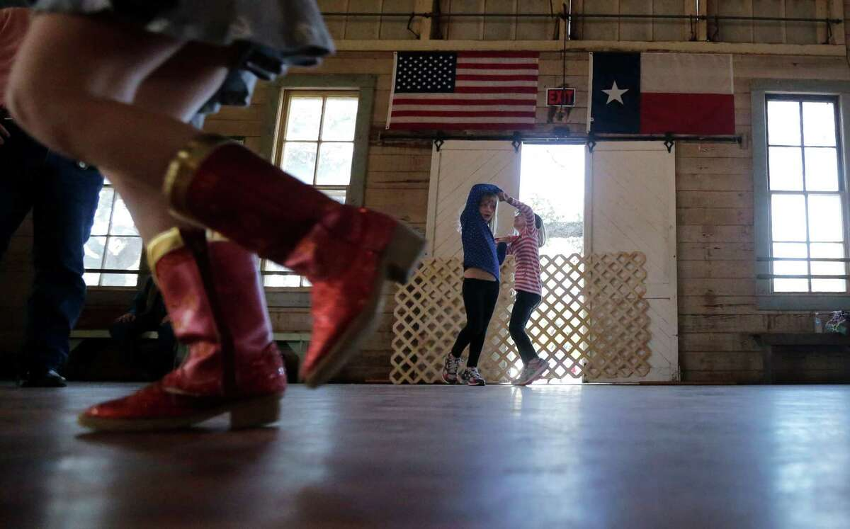 In this Dec. 6, 2014, photo, girls dance to fiddle music at Twin Sisters Dance Hall in Blanco, Texas. A preservation group says old Texas dance halls that for years served as important social centers in rural areas of the state are decaying and closing, with comparatively few still operating. (AP Photo/Eric Gay)