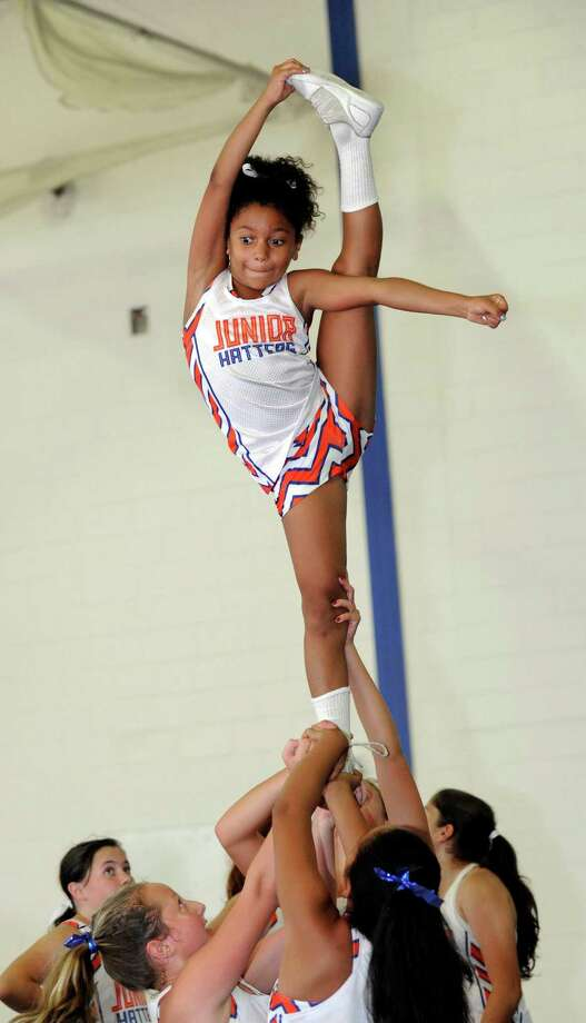 "Ella Brown, 8, of Danbury, a flier for the Danbury Junior Hatters cheerleaders, practices a ""needle"" -  skill requiring extreme flexibility, Thursday, Sept. 10, 2015. Photo: Carol Kaliff / Hearst Connecticut Media / The News-Times"