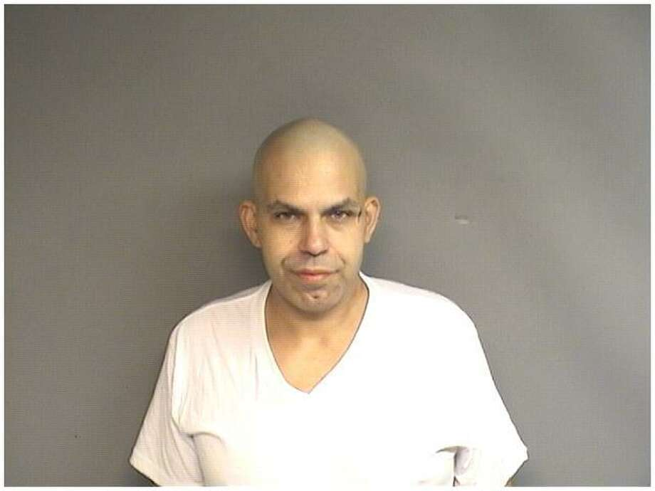 Juan Quinones, 42, from The Bronx, was picked up by narcotics officers in a West Side motel Thursday with a stolen Greenwich gun and over 200 folds of heroin stamped ASAP. Photo: Stamford Police Department / Contributed Photo / Stamford Advocate Contributed