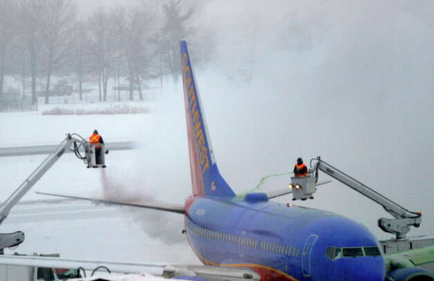 Crews work to clear snow from a departing Southwest Airline 737 Thursday morning Feb. 13, 2014 at the Albany International Airport in Colonie, N.Y.   (Skip Dickstein / Times Union) Photo: SKIP DICKSTEIN