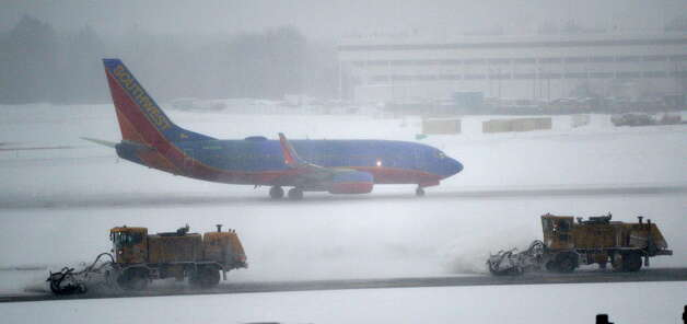 Crews work to clear snow from the taxiway as a Southwest Airliner prepares for takeoff Thursday morning Feb. 13, 2014 at the Albany International Airport in Colonie, N.Y.   (Skip Dickstein / Times Union) Photo: SKIP DICKSTEIN