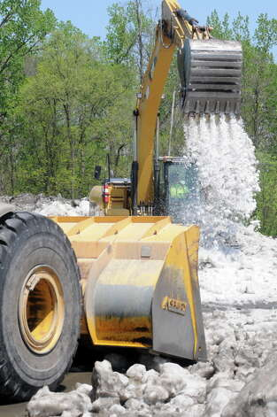 Dick Belknap uses a backhoe to spread out a snow hill still unmelted from winter snow clearing at the Albany International Airport on Friday May 8, 2015 in Colonie, N.Y. (Michael P. Farrell/Times Union) Photo: Michael P. Farrell