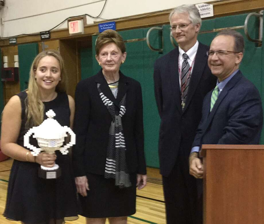 Greenwich High School junior Olivia Hallisey, left, with her Google Science Fair Grand Prize trophy, at the Board of Education's meeting Thursday at Julian Curtiss School.  Joining Hallisey at the podium were, from left, Board of Education Chairman Barbara O'Neill; Superintendent of Schools William McKersie; and Andrew Bramante, Hallisey's honors science research teacher. Photo: Paul Schott