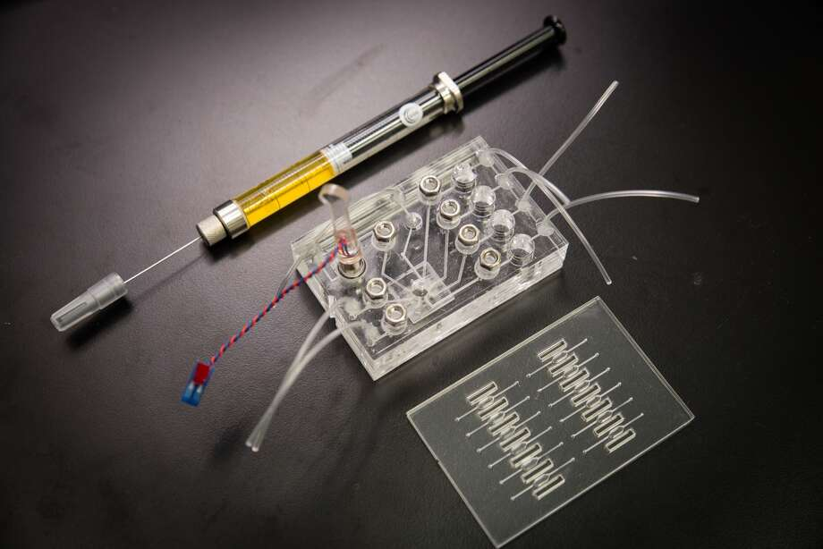 This image shows two key components of a lab-in-a-chip device, with a syringe shown for scale, that can  provide immediate results of certain lab tets.