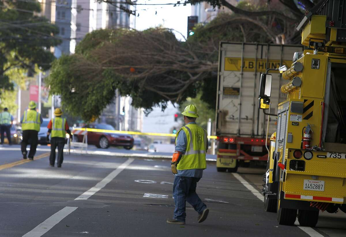 A Muni repair crew waits for a tree to be removed from overhead bus power lines after a big rig clipped the tree which then toppled onto the lines at Mission and Fourth streets in San Francisco, Calif. on Friday, Sept. 25, 2015. Traffic on Mission between Fourth and Fifth streets remained closed while a DPW crew removed the tree and the overhead lines were restored.