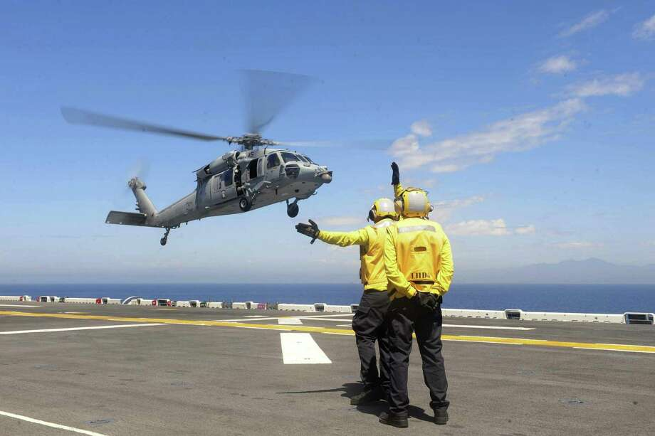 A sailor signals to a Sikorsky MH-60S Seahawk helicopter on the flight deck of the amphibious assault ship USS Boxer during Dawn Blitz 2015 exercises in the Pacific Ocean on September 6, 2015. The Seahawk is assigned to Helicopter Sea Combat Squadron 23. Photo: U.S. Navy Petty Officer 2nd Class Jose Jaen.