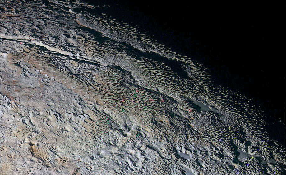 "Pluto's ""snakeskin""In this extended color image of Pluto taken by NASA's New Horizons spacecraft, rounded and bizarrely textured mountains, informally named the Tartarus Dorsa, rise up along Pluto's day-night terminator and show intricate but puzzling patterns of blue-gray ridges and reddish material in between. This view, roughly 330 miles (530 kilometers) across, combines blue, red and infrared images taken by the Ralph/Multispectral Visual Imaging Camera (MVIC) on July 14, 2015, and resolves details and colors on scales as small as 0.8 miles (1.3 kilometers).