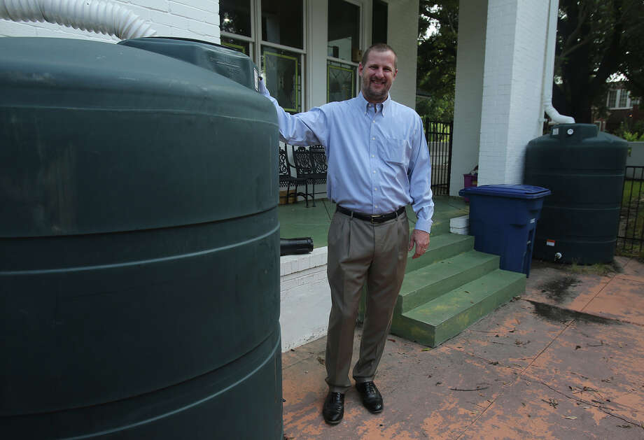 Rainwater harvesting could be more common as the price of treated water increases. Oil and gas attorney Clay Person stands by water tanks he uses at his home to collect rainwater from his roof. Person has 11 tanks with a total capacity of 7,700 gallons. He uses the water for his Monte Vista home's lawn and landscaping. Photo: John Davenport /San Antonio Express-News / ©San Antonio Express-News/John Davenport