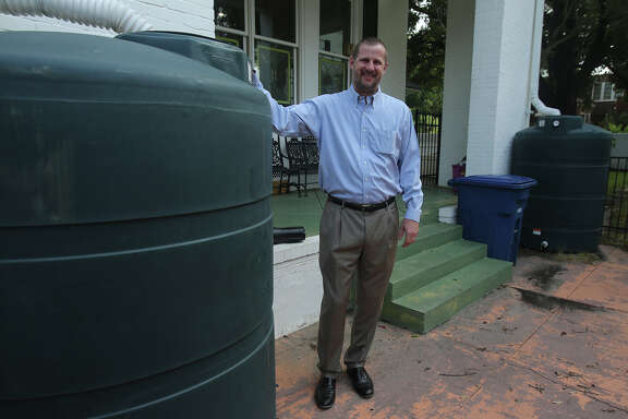 Rainwater harvesting could be more common as the price of treated water increases. Oil and gas attorney Clay Person stands by water tanks he uses at his home to collect rainwater from his roof. Person has 11 tanks with a total capacity of 7,700 gallons. He uses the water for his Monte Vista home's lawn and landscaping.