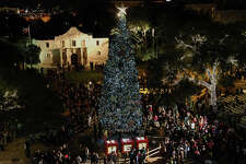 People gather around the 55-foot tall Christmas Tree after the lights were turned on during the H-E-B Tree Lighting Celebration at Alamo Plaza on Nov. 25, 2011. Thousands of LED lights were used to light the tree as well as the surrounding holiday decorations.