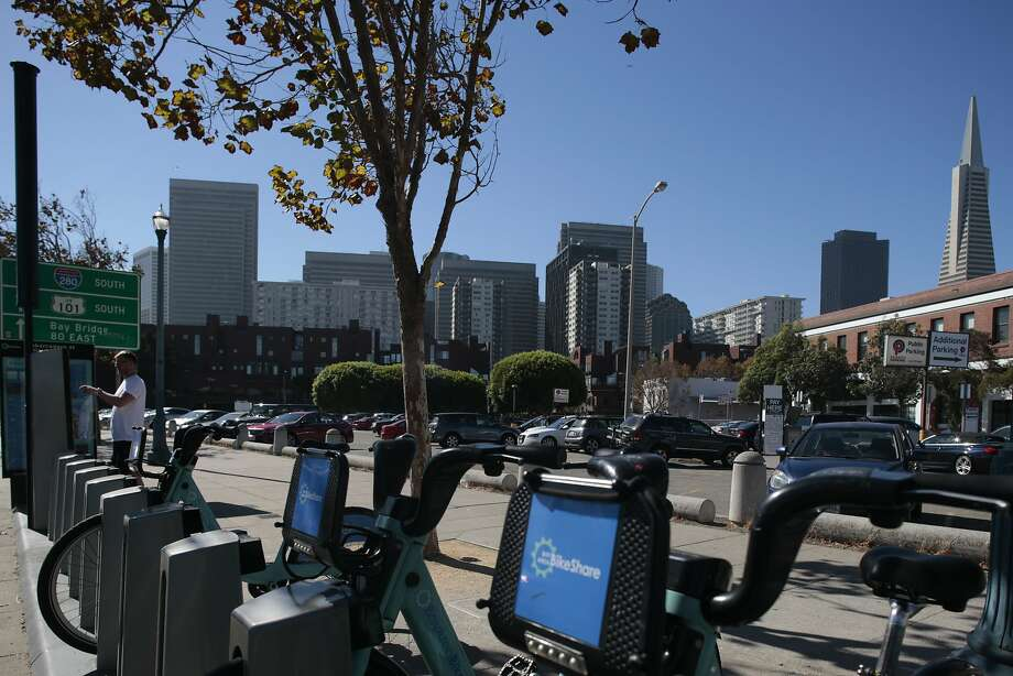 A potential customer reads the directions at the BikeShare rack in front of one of the many public parking lots near  Embarcadero and Broadway on Friday, Sept. 25, 2015 in San Francisco, Calif.  Development proposals are cooking for two long-(mostly)-empty blocks where Broadway meets the Embarcadero, the north side, east of Front Street. Photo: Nathaniel Y. Downes, The Chronicle