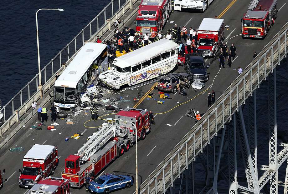 "Emergency personnel work at the scene of a fatal collision involving a charter bus, center left, and a ""Ride the Ducks"" amphibious tour bus on the Aurora Bridge in Seattle on Thursday, Sept. 24, 2015. (Ken Lambert/The Seattle Times via AP)  SEATTLE OUT; USA TODAY OUT; MAGAZINES OUT; NO SALES; TELEVISION OUT; MANDATORY CREDIT: KEN LAMBERT/THE SEATTLE TIMES Photo: Ken Lambert, Associated Press"